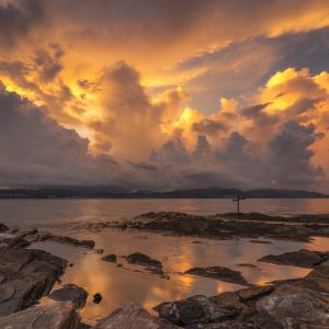 A photograph of a beautiful sunset scene with clouds in a rocky coast taken in Hong Kong, by photographer Kilias Hung