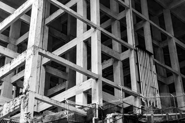 A black and white photograph of a support structure of a high rise building in Hong Kong by Guillaume HOW CHOONG