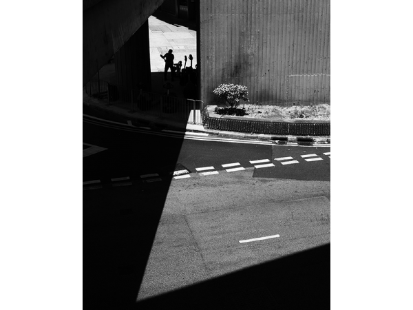 a black and white photograph named backstage by Guillaume HOW CHOONG highlighting the lines of shadows under a bridge over a city road in Hong Kong